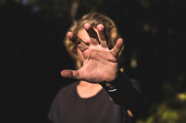 De palm van een hand die zijn gezicht bedekt