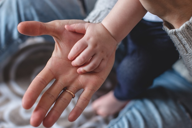 De palmen van de grote man en de kleine kinderen op elkaar. vaders liefde en bescherming. opeenvolging van generaties