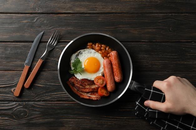De pan van de mensengreep met gebraden eieren op houten lijst, hoogste mening