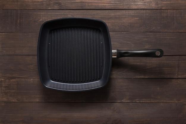 De pan van het gietijzerrooster op houten achtergrond