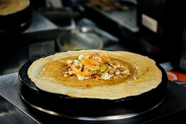 De pannenkoek wordt gebakken en gekookt in een grote ijzeren roti maker pan. indiaas traditioneel straatvoedsel. thaise pannenkoek met banaan, ham en kaas.