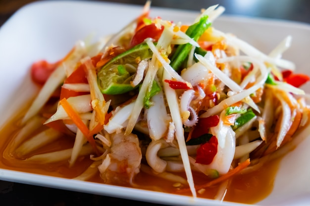 De papajasalade met garnalen en octopus, traditioneel pittig thais eten.