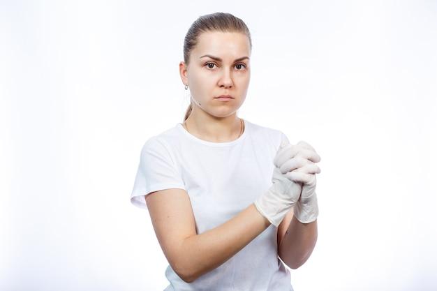 De paramedicus van het meisje trekt witte medische handschoenen aan. bescherming tegen ziektekiemen en virussen. ze is in een wit t-shirt op een witte achtergrond.