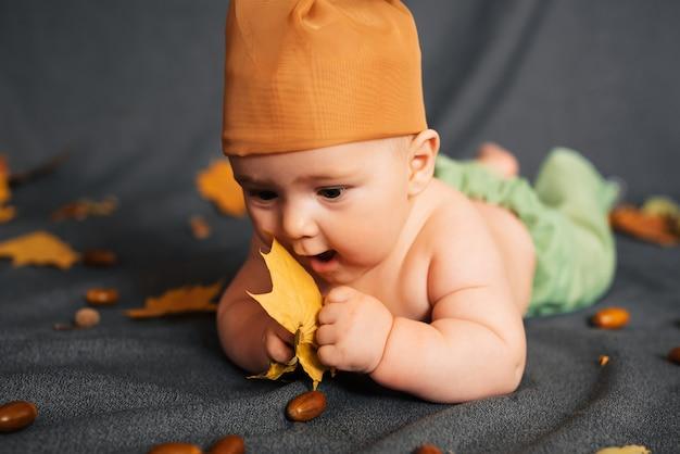 De pasgeboren babyjongen ligt op de bladeren en de eikels van de de herfstesdoorn