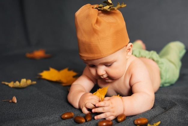 De pasgeboren babyjongen ligt op de herfstachtergrond met esdoornbladeren en eikels