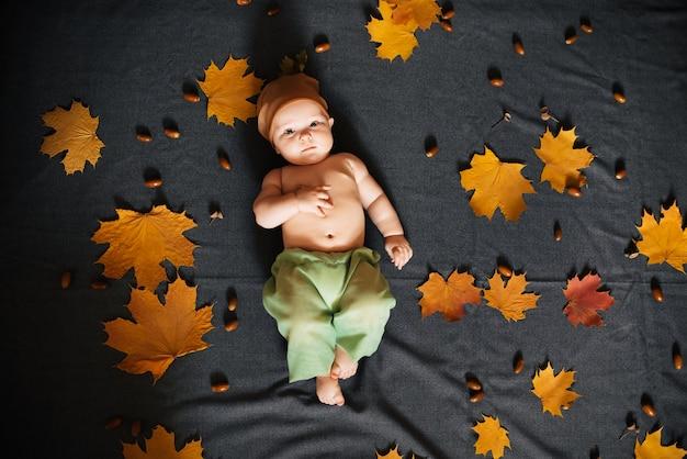 De pasgeboren babyjongen ligt op de herfstbladeren, hoogste mening