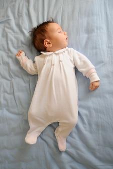 De pasgeboren slaap van het babymeisje op blauwe bladen thuis