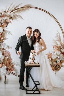De pasgetrouwden gaan een bruidstaart met drie lagen snijden