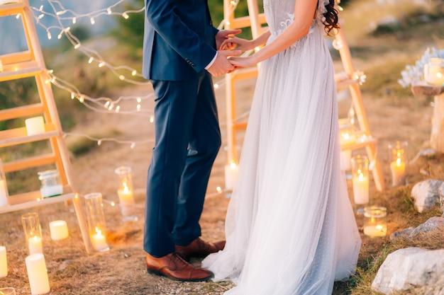 De pasgetrouwden houden elkaars hand vast bij het huwelijksceremoniepaar