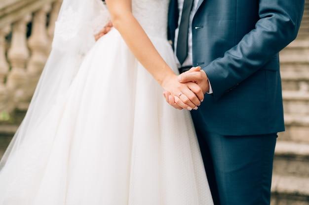 De pasgetrouwden houden elkaars hand vast, paar hand in hand bruiloft