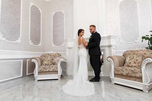De pasgetrouwden kijken elkaar zacht aan. de bruid en bruidegom knuffelen zachtjes binnenshuis.