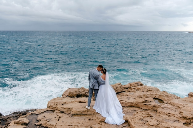 De pasgetrouwden knuffelen zachtjes op de rotsen bij de zee en genieten van de natuur van cyprus