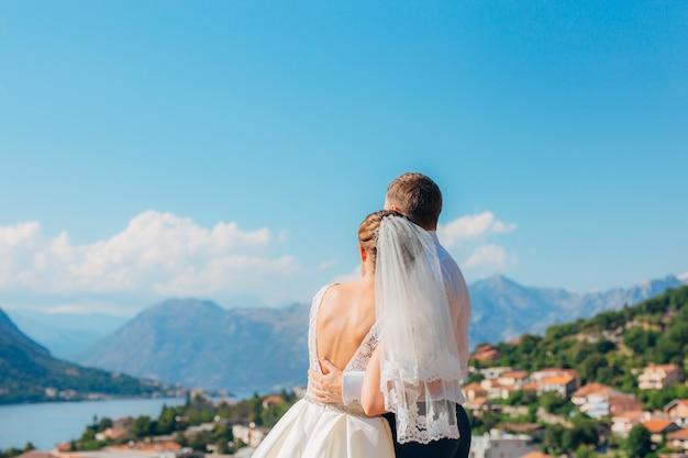 De pasgetrouwden omhelzen en kijken naar de baai van kotor in montenegro