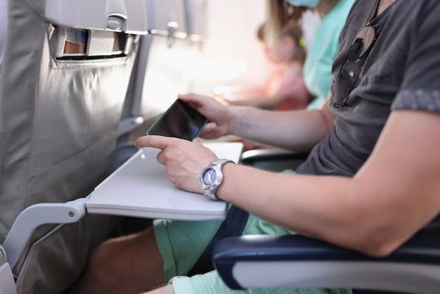 De passagier van het vliegtuig zit stil en houdt de telefoon in zijn handen.