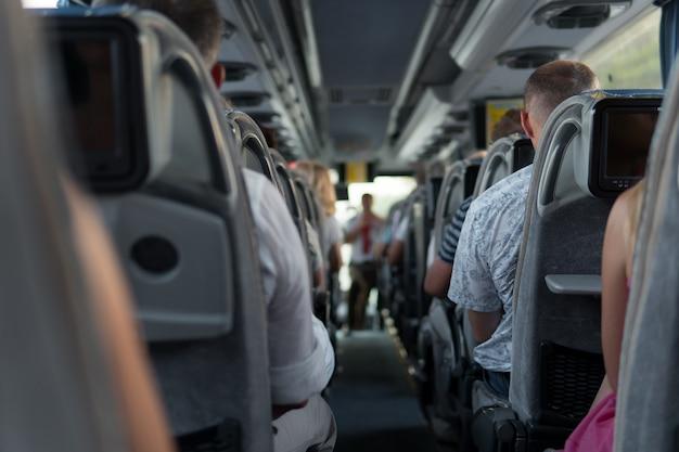 De passagiers in de bus tijdens de reis met toeristen en rondleiding.