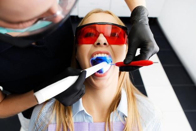 De patiënt in rode glazen zit als voorzitter op het tandartskantoor terwijl de arts haar tanden wittert