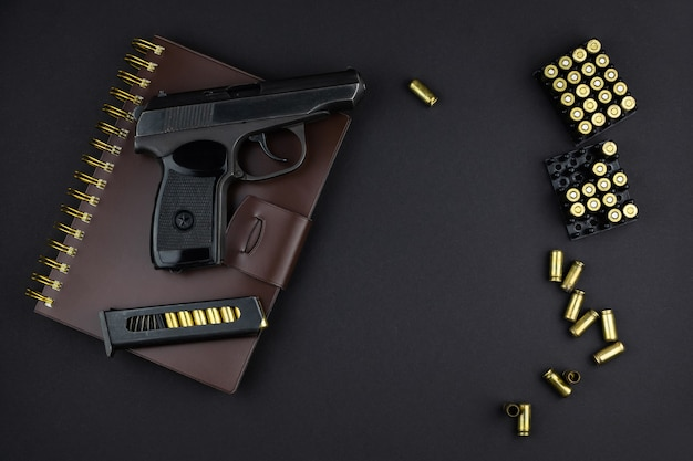 De patronen, het pistool en het geladen magazijn ervoor liggen op een bruin leer gebonden notitieboekje