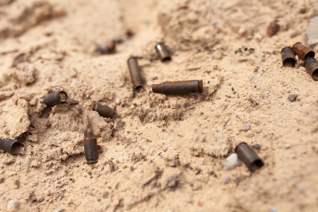 De patronen van de cartridges liggen in het zand