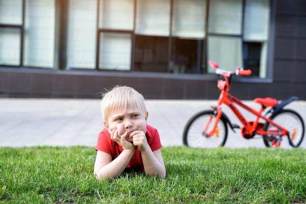 De peinzende blonde jongen rust op het gazon. fiets op de achtergrond