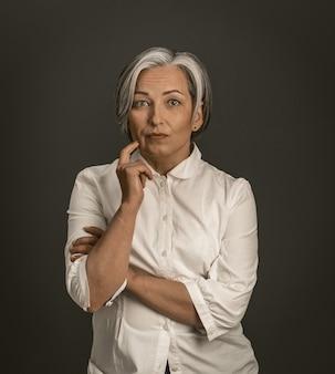 De peinzende vrouw raakt gezicht met hand terwijl het bekijken camera. rijpe dame in wit overhemd dat op grijze achtergrond wordt geïsoleerd. brain storm concept. getint beeld.