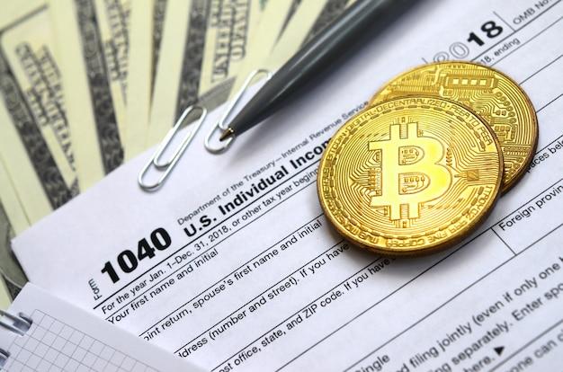 De pen, bitcoins en dollarbiljetten liggen op het belastingformulier 1040 us individual income tax return. de tijd om belasting te betalen