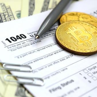 De pen, bitcoins en dollarbiljetten liggen op het belastingformulier 1040 us