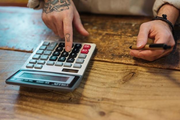 De pen die van de jonge mensenholding calculator in zijn winkel met behulp van