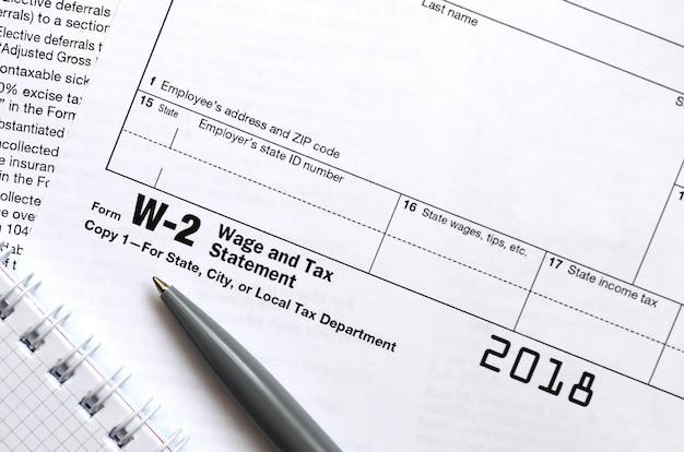 De pen en het notitieboekje op het belastingvorm w-2 loon en de verklaring van de belasting. de tijd om belasting te betalen