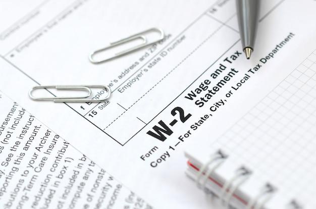 De pen en het notitieboekje op het belastingvorm w-2 loon en de verklaring van de belasting.