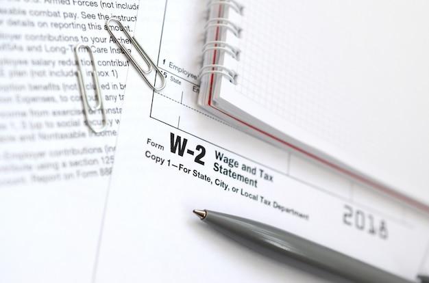 De pen en het notitieboekje op het belastingvorm w-2 loon en de verklaring van de belasting