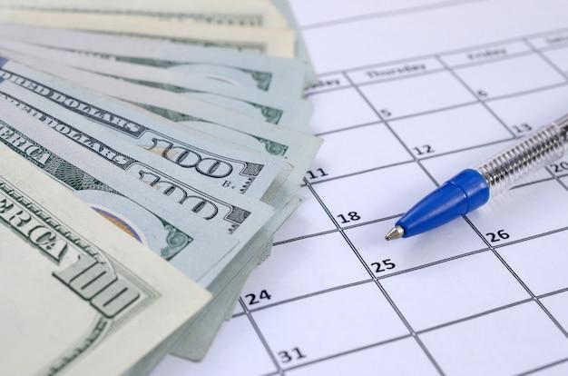 De pen en vele honderd amerikaanse dollarsrekeningen op kalenderpagina sluiten omhoog