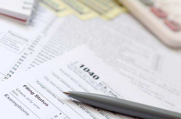 De pen-, notebook-, calculator- en dollarbiljetten liggen op het belastingformulier 1040 us individual income tax return. de tijd om belasting te betalen
