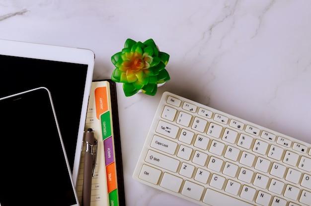 De pen van conceptenplanning op notitieboekje wekelijkse kalender met smartphone en computertoetsenbord