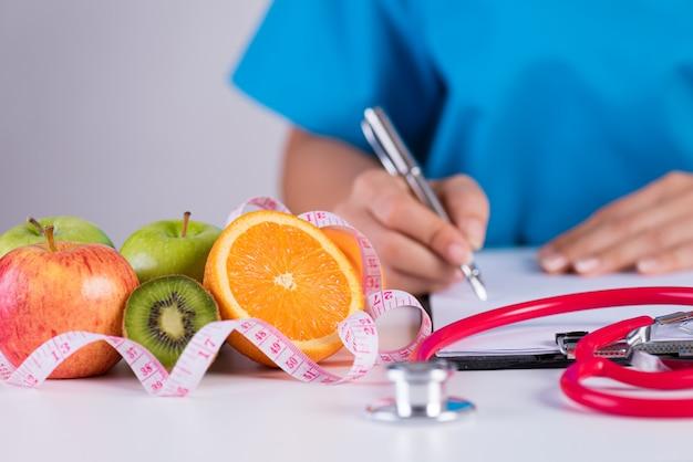 De pen van de artsenholding met controlelijst en groenten, gezondheidszorgconcept.