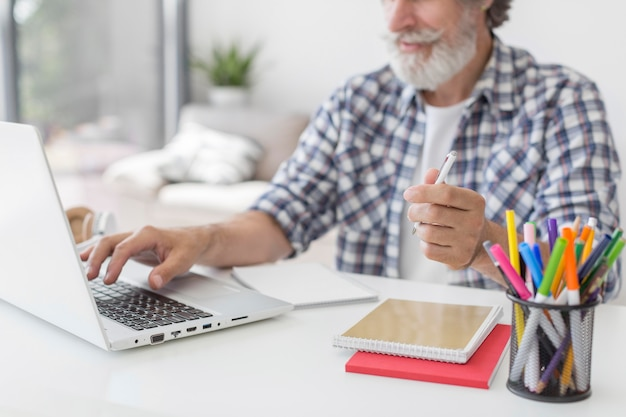 De pen van de leraarsholding die laptop met behulp van