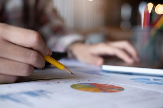 De pen van de vrouwenholding die calculator gebruiken met analyseert grafiekgrafiek en computerlaptop voor winstvoorspelling in de toekomst.