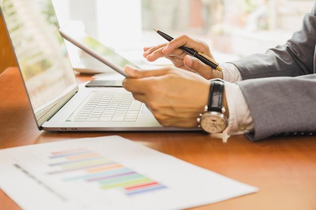 De pen van de zakenmanholding en het gebruiken van tablet en laptop die aan financieel plan werken.