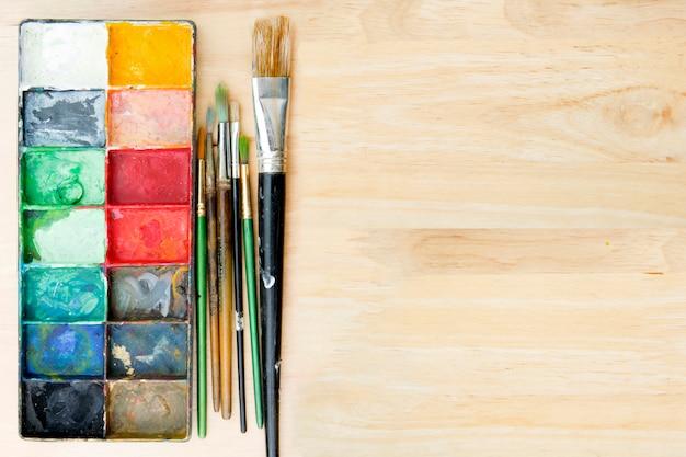 De penselen en het palet van de kunstenaarsverf op houten achtergrond