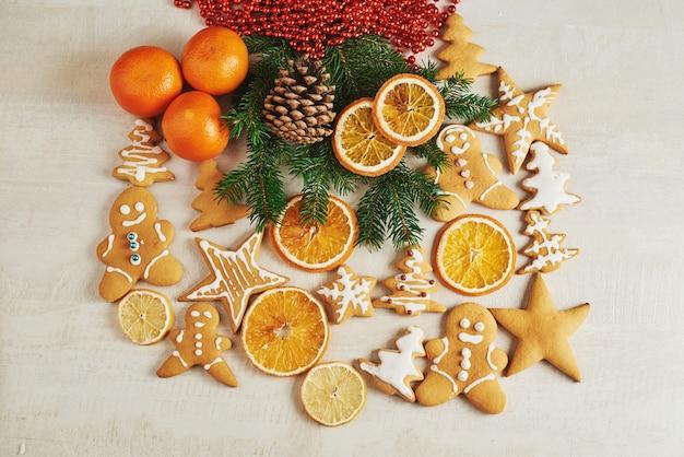 De peperkoekkoekjes van kerstmis en droge sinaasappel en kruiden op witte lijst. stoelen kerstbomen, kegels en kerstversiering