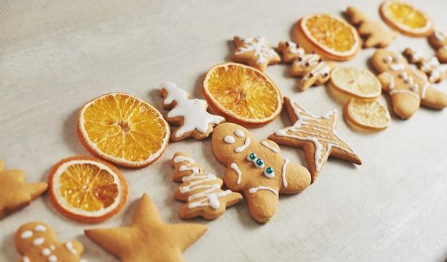 De peperkoekkoekjes van kerstmis en droge sinaasappel en kruiden op witte lijst