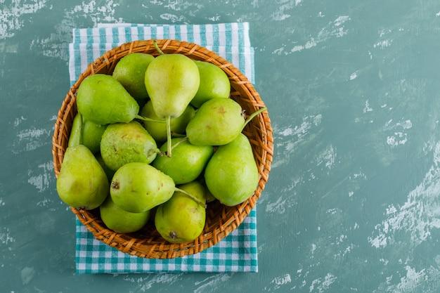De peren in een mandvlakte leggen op pleister en keukenhanddoekachtergrond