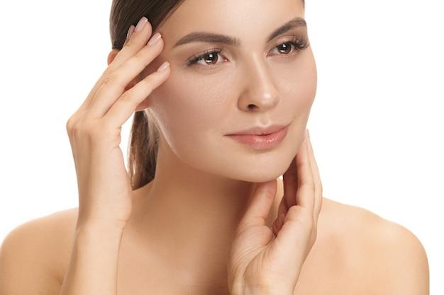 De perfecte en schone huid van het gezicht van de vrouw op een witte muur