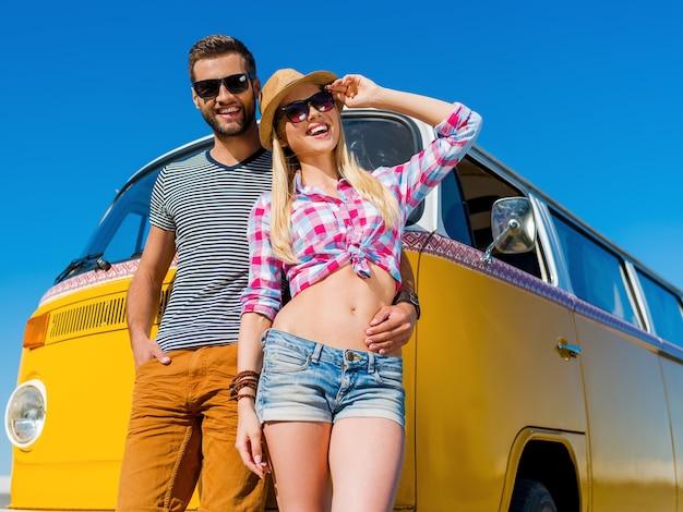 De perfecte zomerdate. vrolijke jongeman die zijn vriendin omhelst terwijl ze allebei naar hun retro minibusje leunen