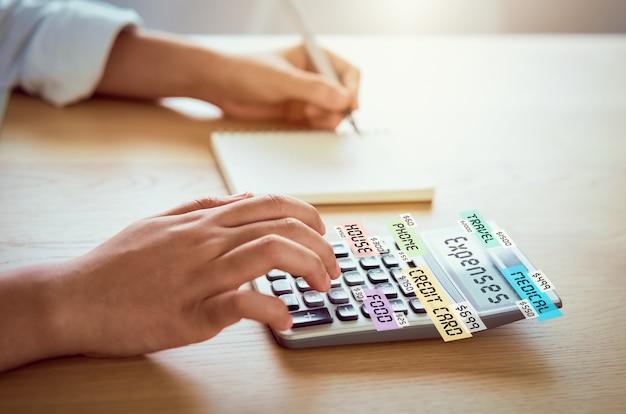 De perscalculator van de vrouw om inkomensuitgaven en plannen voor zakgeld aan huisbureau te berekenen.