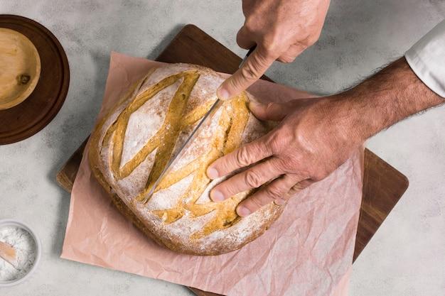 De persoon die de helft van brood plat snijdt lag