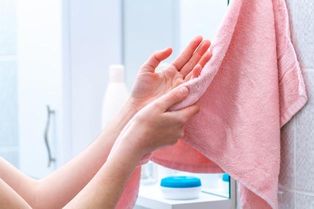 De persoon die handdoek voor het afvegen van handen gebruikt droogt thuis na was in badkamers. hygiëne en handverzorging