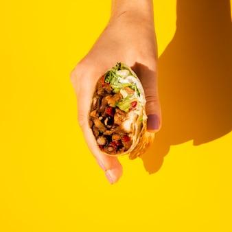 De persoon die van de close-up smakelijke burrito houdt