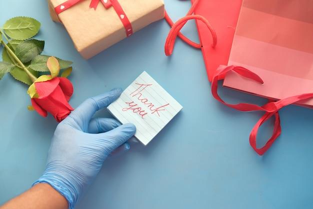 De persoon dient latexhandschoenen in houdend bedankbrief