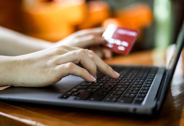 De persoon heeft een creditcard en vult zijn creditcardgegevens in om online voor goederen te betalen. creditcards kunnen zowel in de winkel als online winkelen voor goederen en diensten betalen.