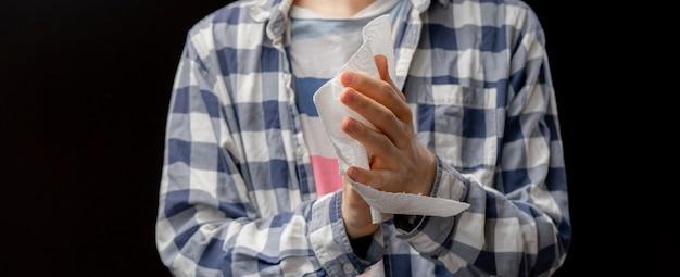 De persoon maakt schoon of veegt zijn handen met nat document servet af